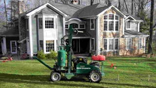 Photo of Terra;ift machine in front of large stone-faced residential home; the Terralift is used by Statewide Environmental Services in their septic field restoration services.
