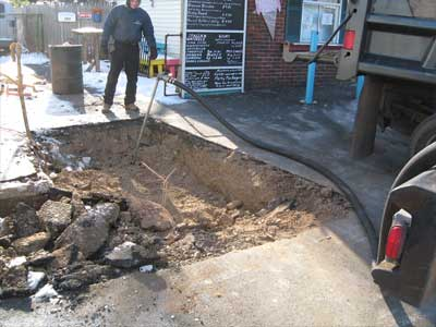 Photo of technician sweeping excavation to locate underground oil tank on commercial property.